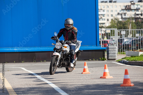 Woman L-driver driving slalom through the cones on training ground on motorcycle