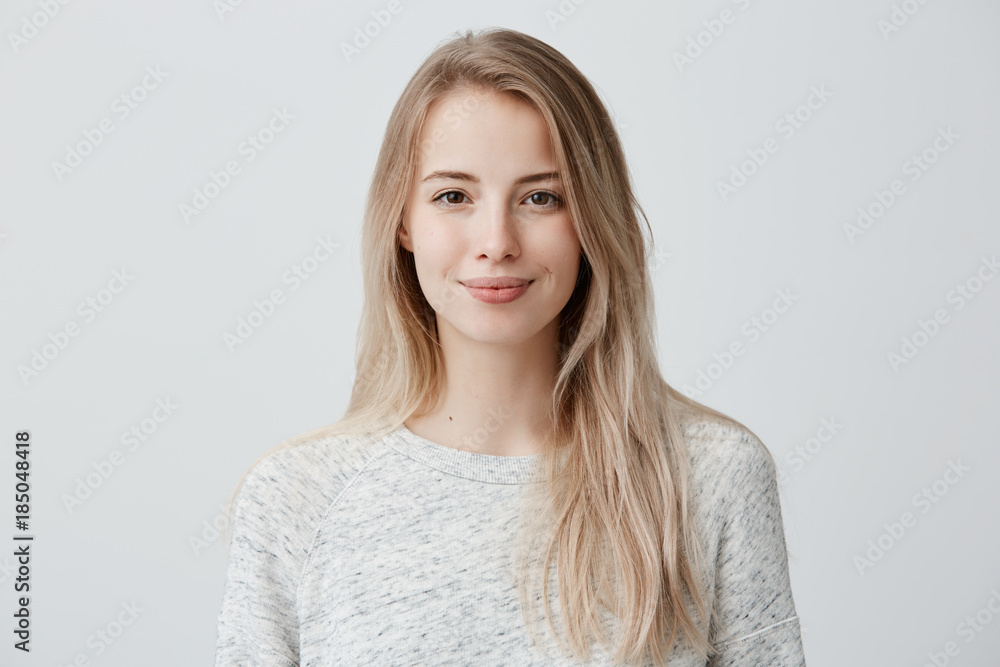 Fototapeta Pretty smiling joyfully female with fair hair, dressed casually, looking with satisfaction at camera, being happy. Studio shot of good-looking beautiful woman isolated against blank studio wall.