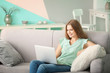 Beautiful woman using laptop while resting on sofa at home