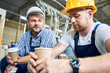 canvas print picture - Portrait of two workers wearing hardhats taking break from work drinking coffee and resting sitting on construction site