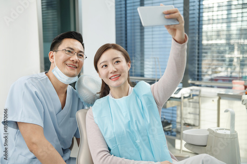 Male dentists and female patients use mobile phones to take pictures