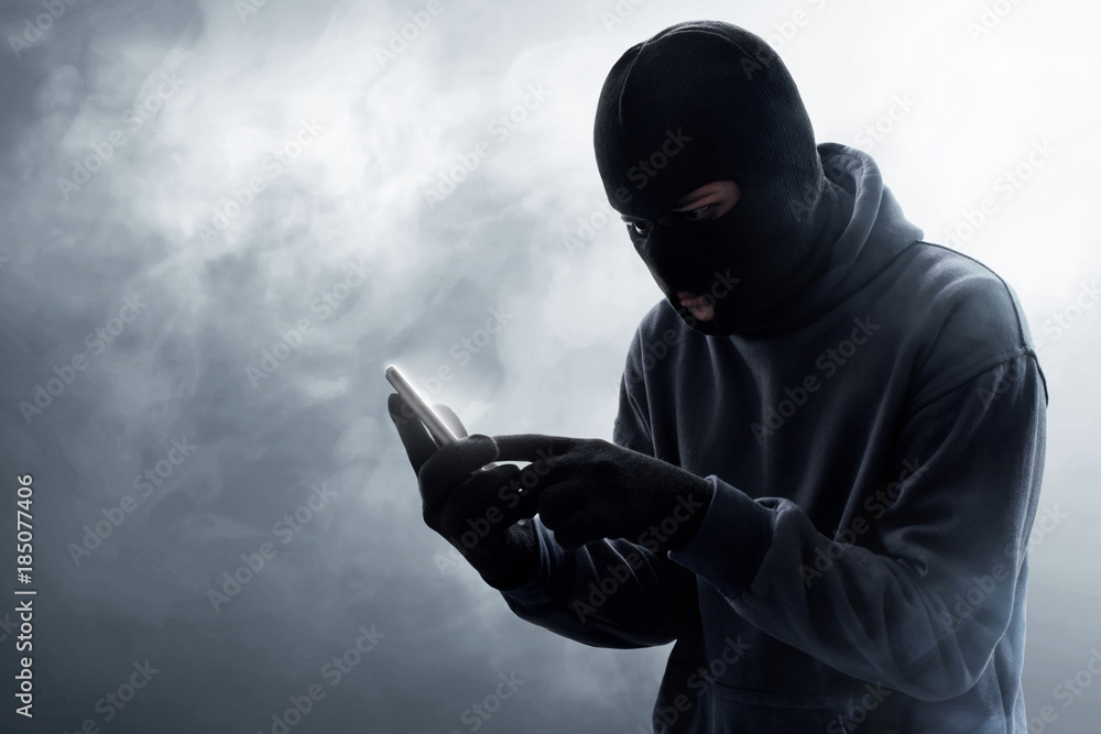 Fototapeta Masked thief using mobile phone