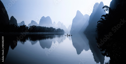 Person on rowboat in Li River at sunrise, China