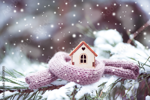 Obraz Christmas Toy house is wrapped in a warm scarf, it's snowing.on a natural natural background of a real fir in the snow, toned. Concept of winter, Christmas, new year, - fototapety do salonu