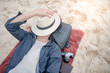 Young Asian man lying on the beach and close his face by hat, vacation time and summer holiday concepts