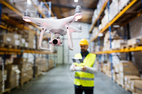Obraz Man with drone in a warehouse. - fototapety do salonu