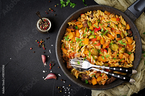 Photo  Fusilli vegetable paste with pumpkin, Brussels sprouts, paprika and liver pieces on a dark background