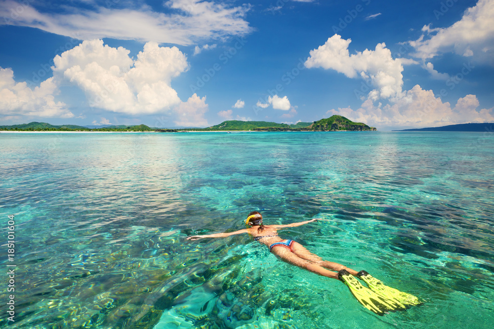 Fototapeta Woman snorkeling in clear tropical waters on a background of exotic islands.