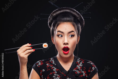 Poster Sushi bar Surprised Asian woman eating sushi and rolls on a black background.