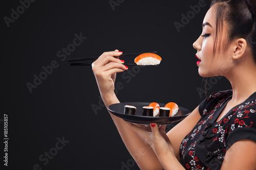 Fototapeta Asian woman eating sushi and rolls on a black background. obraz