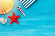 Summer board of sea shells scallop and star fish on blue wooden background