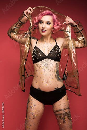 8ba3581bf sexy pin up girl with tattoos in lingerie and raincoat infront of red  background