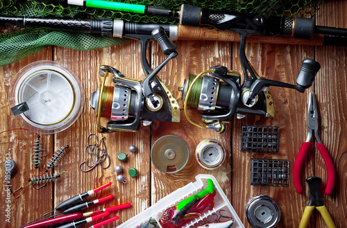 Poster Peche Fishing rods and spinnings in the composition with accessories for fishing on the old background on the table