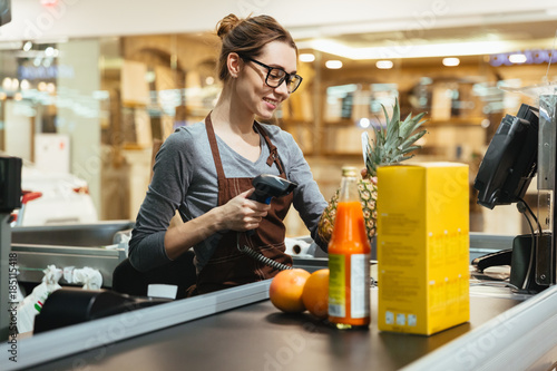 Fotomural Smiling female cashier scanning grocery items