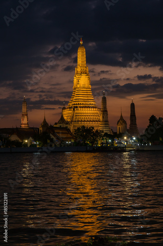 In de dag Bangkok Pagoda at temple of dawn or Wat Arun in Bangkok, Thailand when sunset at twilight with scattered cloud and blue sky in the background and Chao Phraya river in the foreground.