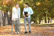 Young caregiver walking with senior man in park