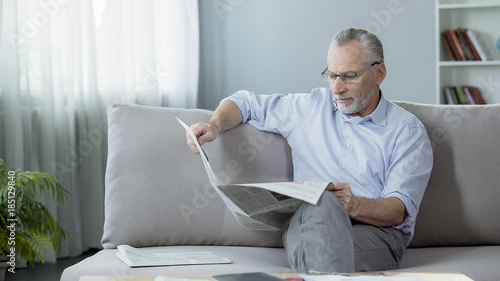 Fotografie, Obraz  Senior male sitting on sofa and reading newspaper, press and news, rest time