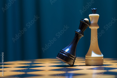 Photo Chess black queen and white king stand on a wooden chessboard