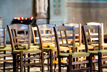 A Close Up View Of Wooden Chairs With Green Wicker Seats Lined Up In Front Of A Rack Holding Lit Votive Candles.