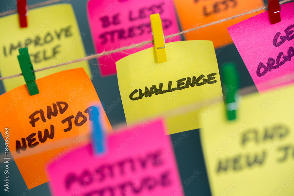 Colorful sticky notes with positive affirmation words and phrases hung from a clothesline by clothespins.