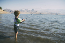 Side View Of Boy Fishing While Standing In River During Sunny Day