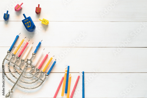 Hanukkah/ Chanukah Jewish holiday background with menorah (Judaism candelabra) burned candles and traditional Dreidrel game toy on white wood table backdrop