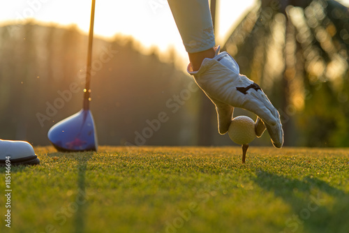 Spoed Foto op Canvas Golf Hand asian woman putting golf ball on tee with club in golf course on evening and sunset time a for healthy sport. Lifestyle Concept.
