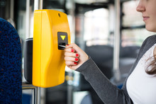 Young Woman Hand Inserts The Bus Ticket Into The Validator, Validating And Ticking