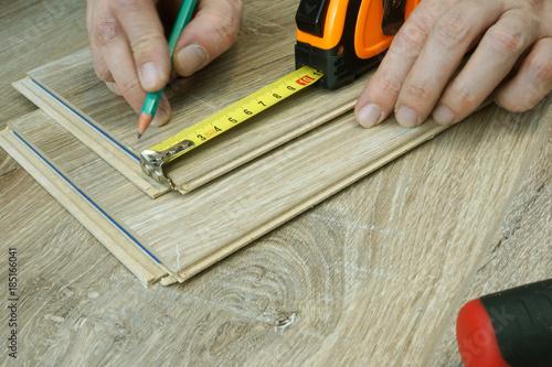 Man Preparing For Installation Of Laminate Flooring Renovation Of