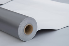 Waterproofing And Insulation At Construction Site, Opened Pvc Membrane Roll Lying On Roof Closeup. Copy Space For Your Text.