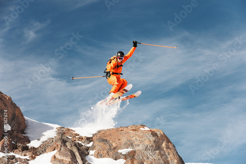An athlete skier is jumping from high rock high in the mountains.