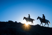 Silhouetted Western Cowboy And Cowgirl On Horseback Against A Blue Sky With Sun Flare At Horizon