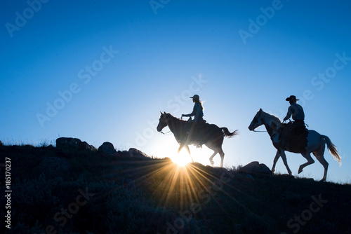 Silhouetted Western Cowboy and Cowgirl on horseback against a blue sky with sun Wallpaper Mural