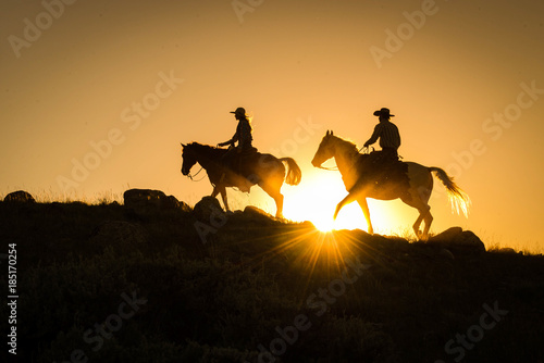 Silhouetted western cowboy and cowgirl on horseback against yellow sunset Canvas Print