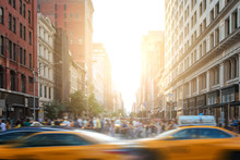 Fast Paced Motion In New York City As Yellow Taxi Cabs Speed Down 5th Avenue With Crowds Of Busy People Walking Across The Intersection At 23rd Street In Manhattan With Sunset Light In The Background