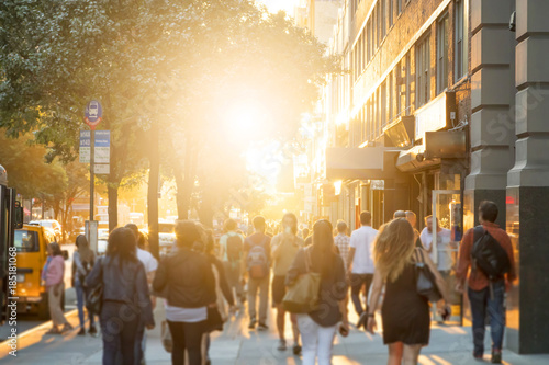 Man stands in the middle of a busy sidewalk looking at his cell phone while crowds of people walk around on 14th Street in Manhattan, New York City with the glow of sunlight in the background. - 185181068