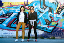Two Pretty Girls Posing On A Spring Day In Front Of Graffiti On The Wall In Background