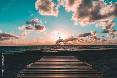 Photo beach chair perspective of teal and pink tones in the sky over the ocean as the