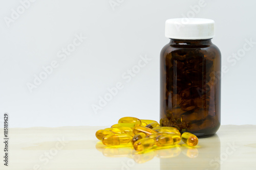 Fotografie, Obraz  Yellow fish oil capsule pills with amber glass bottle with blank label on the table with copy space for text