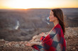 Beautiful woman wrapped in kaftan blanket meditating at sunset overlooking a canyon