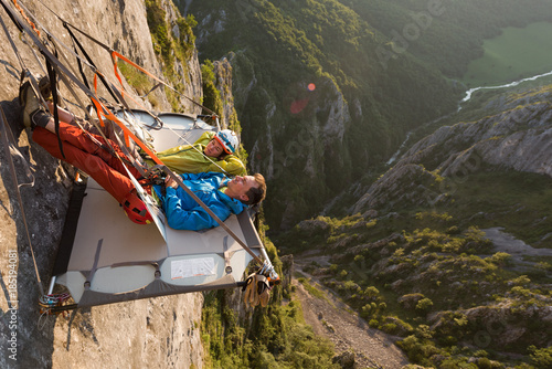 Poster Ontspanning Rock climbing couple laying down on their portaledge