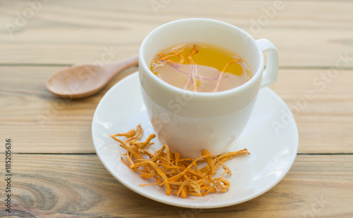 .Dried Cordyceps Militaris Mushroom with Cup on wooden table background