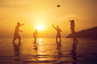 Silhouette of people playing at the beach in summer sunset