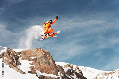 An athlete skier is jumping from high rock high in the mountains. Slika na platnu