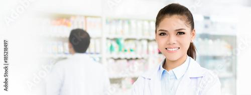 Poster Pharmacie Smiling Asian female pharmacist in chemist shop or pharmacy