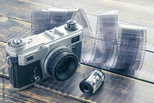 Fotomural  Old film camera, black and white film and film roll on a wooden
