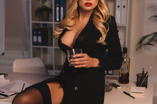 Cropped Image Of Seductive Woman Holding Glass Of Whiskey In Office At Evening
