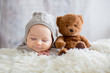 Leinwandbild Motiv Sweet baby boy in bear overall, sleeping in bed with teddy bear