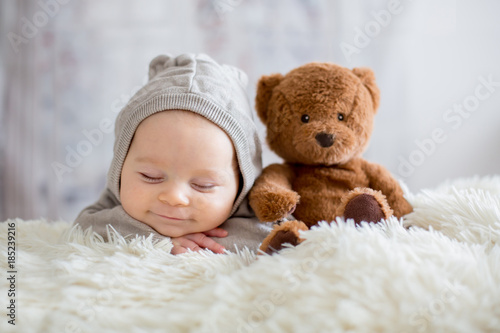 Cuadros en Lienzo Sweet baby boy in bear overall, sleeping in bed with teddy bear