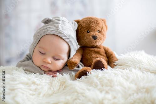 Fototapeta Sweet baby boy in bear overall, sleeping in bed with teddy bear obraz na płótnie
